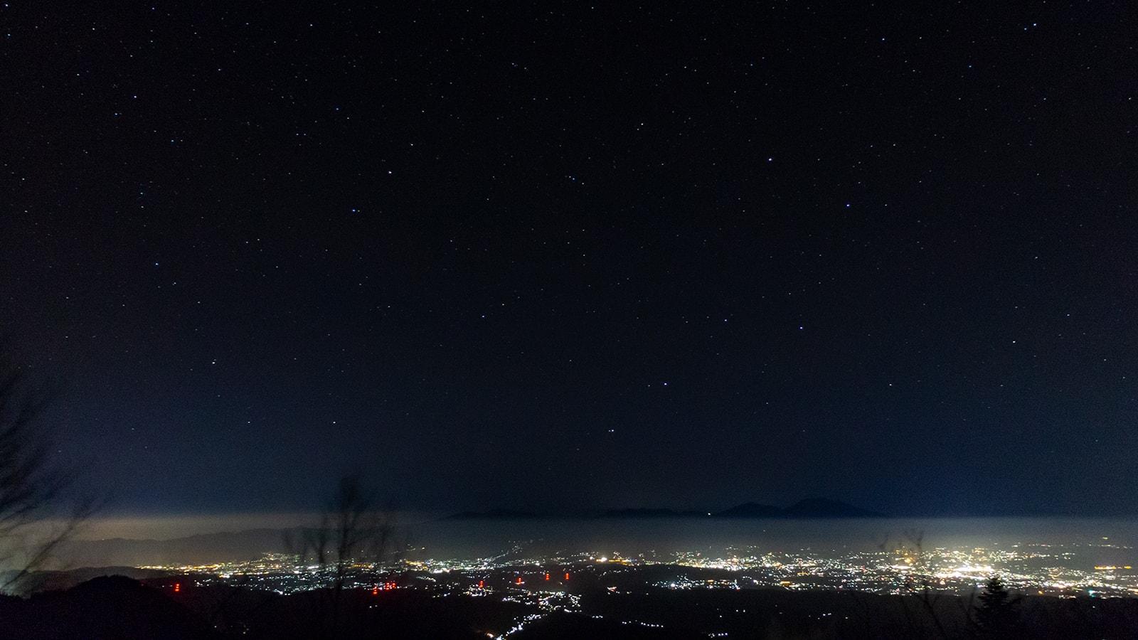 佐久市にある大河原峠からは佐久平の夜景と星空の大パノラマが広がる